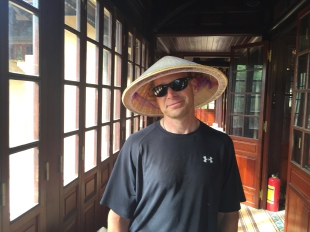 Wearing a Vietnamese conical hat, or non la